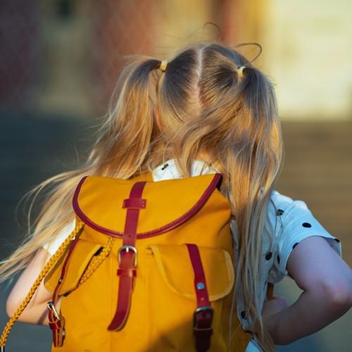niña corriendo con mochila amarilla