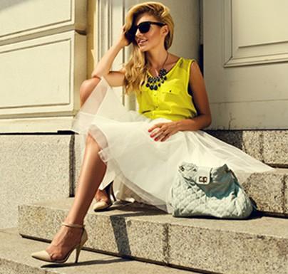 mujer sentada con con vestido elegante y gafas de sol