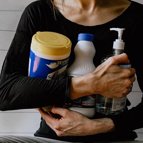 mujer sujetando productos de limpieza