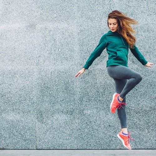 mujer saltando con ropa de deporte